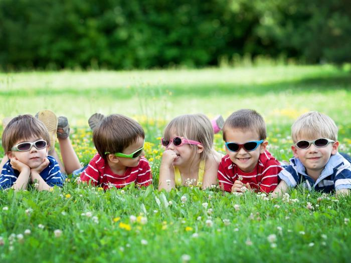 Five children in sunglasses on grass